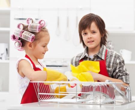 uso domestico: I bambini che fanno i piatti insieme in cucina - primo piano sulla zona lavello