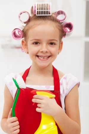 Little girl with cleaning utensils and a big grin photo