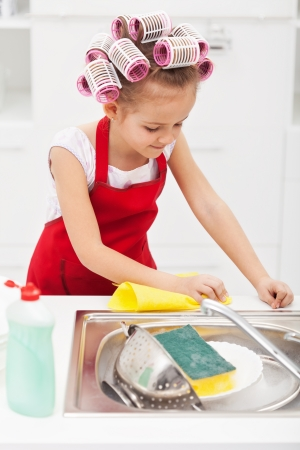 household chores: Little girl cleaning the kitchen - wiping the sink area, wearing big hair curls Stock Photo