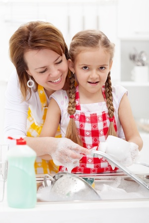 household tasks: Little girl washing dishes helped by her mother - closeup Stock Photo