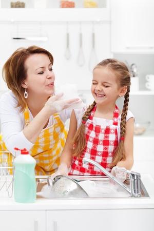 lavar trastes: Mujer y niña que se divierten lavar los platos - jugando con la espuma