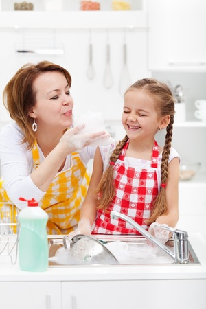 house chores: Woman and little girl having fun washing the dishes - playing with the foam Stock Photo