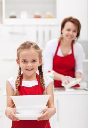 접시를 들고 요리를 할 수있는 작은 girtl의 도움의 어머니 스톡 콘텐츠