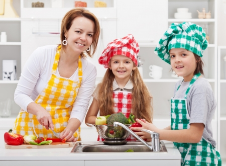 Kids helping mother preparing a salad in the kitchen - washing the vegetables Stock Photo - 19337290