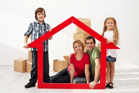Happy family with two kids moving into their new home - sitting among cardboard boxes Stock Photo - 19505416