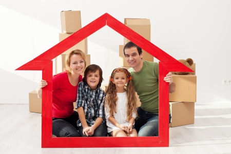 home insurance: Family with kids portrait in their new home - with cardboard boxes and house shaped frame Stock Photo