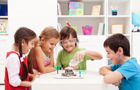 Kids repeating and observing a science lab project at home - the baking soda and vinegar volcano Stock Photo