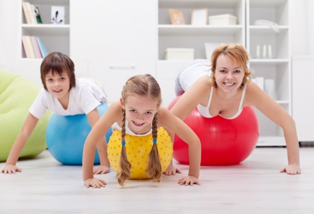 kids exercise: Happy healthy family exercising doing push ups on large balls - at home Stock Photo