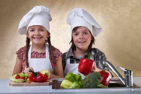 slicing: Happy kids washing vegetables for a salad - chopping them up for a meal Stock Photo