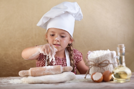 a young family: Little girl stretching the cookie dough dispersing some flour over it