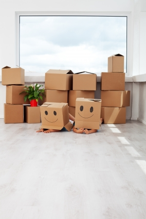 moving activity: Kids having fun while moving in a new home - laying with cardboard boxes