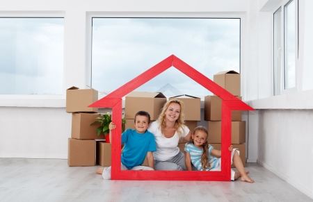moving activity: New home concept with woman and kids and lots of cardboard boxes in empty room
