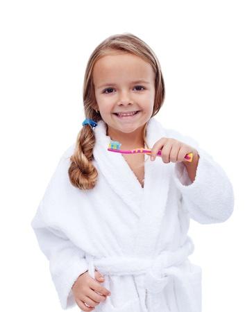 health education: Little girl in bathrobe washing teeth after bath