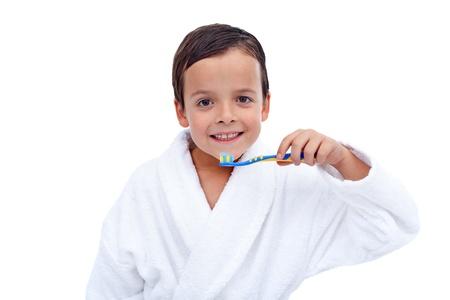 Little boy in bathrobe washing his teeth after evening bath photo