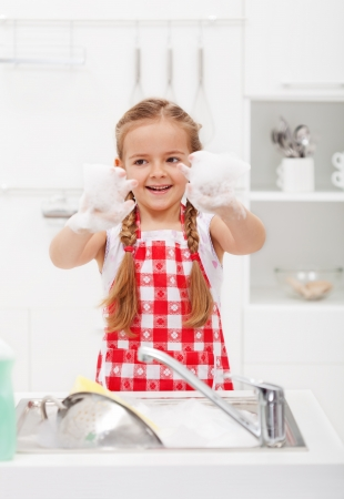 dish washing: Happy little girl washing the dishes having fun with the foam Stock Photo