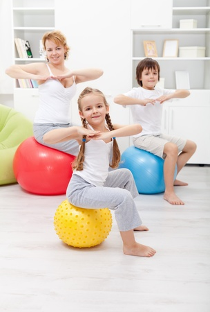 Woman doing gymnastic exercise with the kids at home