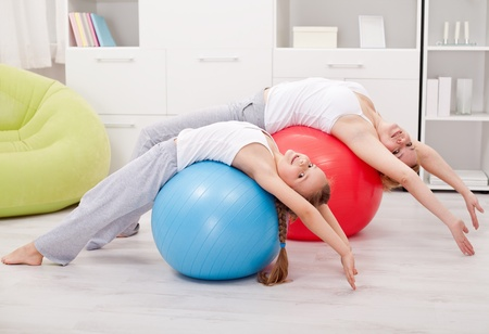 Stretching exercises at home - woman and little girl on large gymnastic balls