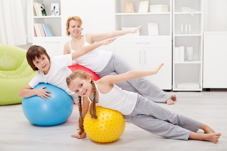 Kids exercising with their mother using large gymnastic balls Zdjęcie Seryjne