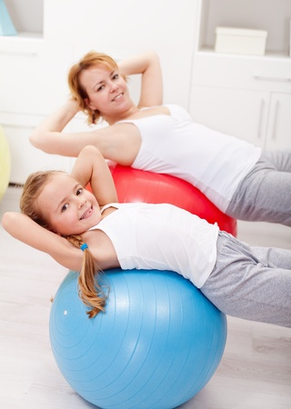 Woman and little girl exercising with large balls at home Zdjęcie Seryjne