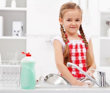 lavare piatti: La bambina lavaggio piatti in cucina - primo piano