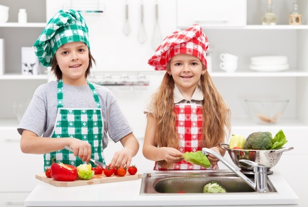 Kids helping in the kitchen - washing and slicing vegetables for a meal Zdjęcie Seryjne