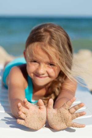 Happy little girl with sandy hands laying on deck chair by the sea - focus on hands photo