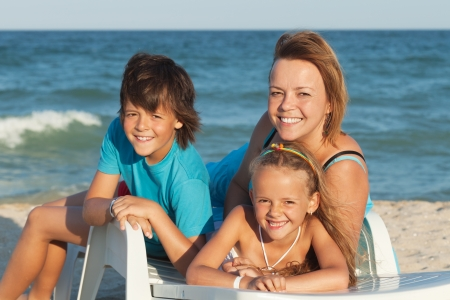 Happy woman and kids relaxing on a deck chair by the sea - summer beach portrait