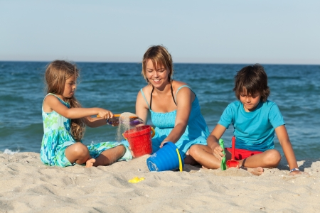 Woman and kids on the beach - playing with sand Stock Photo