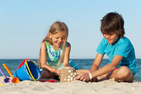 Kids playing on the beach building a sand castle decorating it with seashells Foto de archivo