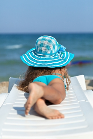 Little girl on the beach relaxing on a deck chair watching the sea photo