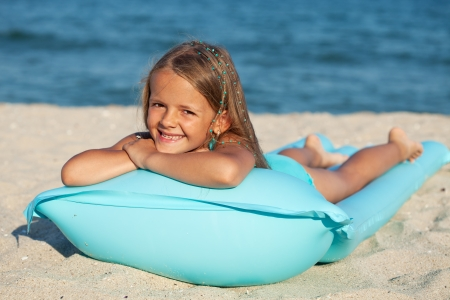 Little girl with inflatable mattress or raft on the beach sunbathing photo