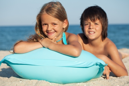 Kids with inflatable raft at the beach - sunny portrait photo