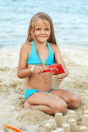 children sandcastle: Little girl playing with sand on the beach - building little towers