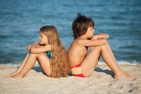 bambini pensierosi: I bambini di relax in spiaggia - ragazzo e ragazza seduta sulla sabbia