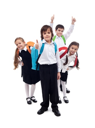 ni�os en la escuela: Grupo de ni�os felices con mochilas de regresar a la escuela despu�s de las vacaciones de verano