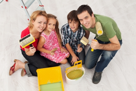 Happy family redecorating their home - sitting together with painting utensils photo