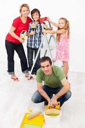 Young family with two kids repainting their home together photo