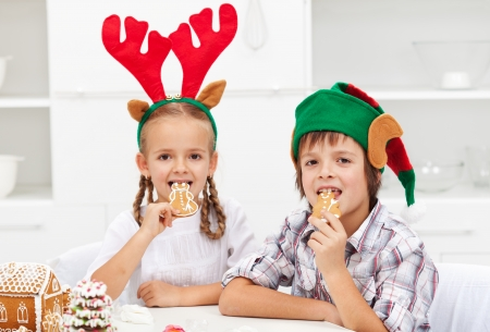 munching: Kids with funny christmas hats munching on gingerbread cookies