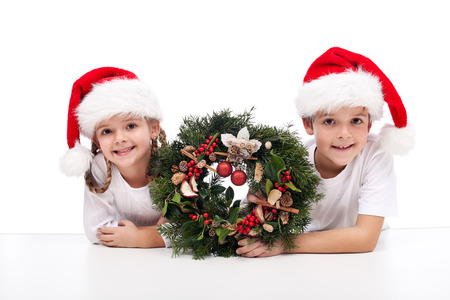 Kids with traditional advent wreath wearing santa hats Zdjęcie Seryjne - 22426647