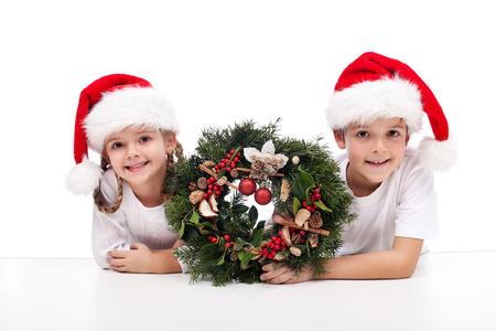 corona de adviento: Los niños con corona de adviento tradicional, llevando sombreros de santa Foto de archivo