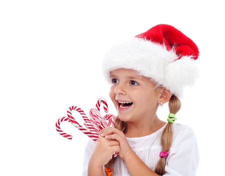 Happy laughing christmas hat girl with candy cane sweets - isolated photo