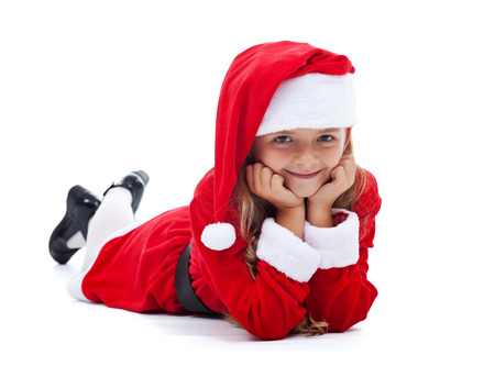 Happy girl in Santa outfit smiling laying on the floor- isolated photo