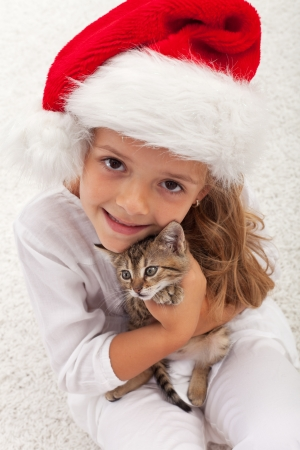 The best christmas present ever - happy little girl with her new kitten photo