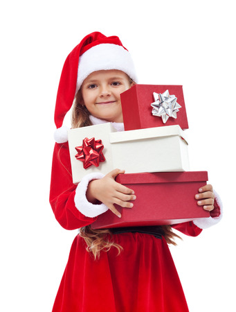 Happy little girl in santa costume holding christmas presents - isolated photo