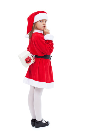 x mas: Girl in santa costume preparing a surprise holding a present - isolated