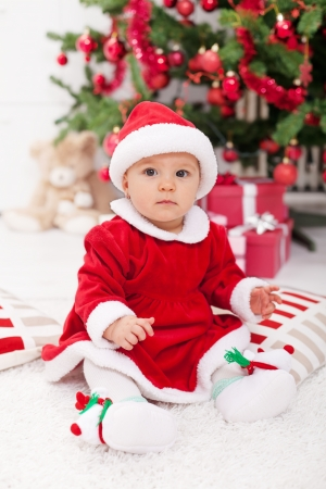 Pretty baby girl in santa costume sitting by the christmas tree photo