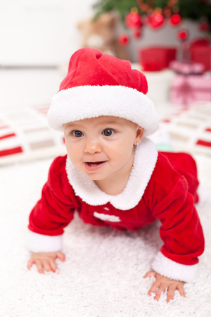 Baby girl in santa outfit crawling in front of the christmas tree photo