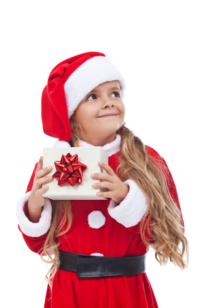Happy little girl in santa outfit holding christmas present - isolated photo