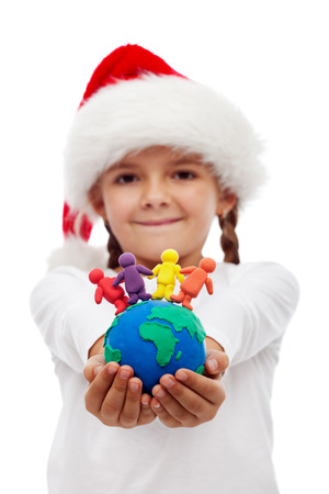One world of happy people at christmas concept - little girtl holding earth and people made of clay, isolated photo