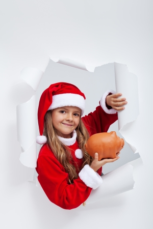 Little santa girl saving for christmas presents - looking through hole in paper, with copy space photo